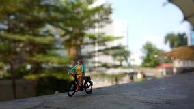 Fim acima dos brinquedos de Mini Figure Woman que bicycling na maneira do trajeto do lado do rio com espaço negativo ou da cópia  imagem de stock royalty free