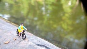 Fim acima dos brinquedos de Mini Figure Woman que bicycling na maneira do trajeto do lado do rio com espaço negativo ou da cópia  foto de stock