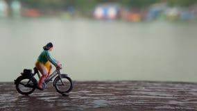 Fim acima dos brinquedos de Mini Figure Woman que bicycling na maneira do trajeto do lado do rio com espaço negativo ou da cópia  imagem de stock