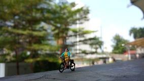 Fim acima dos brinquedos de Mini Figure Woman que bicycling na porta de construção com espaço negativo ou da cópia para a colocaç foto de stock royalty free