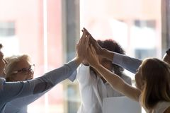 Fim acima dos empregados diversos que dão altamente cinco na reunião de empresa imagens de stock royalty free