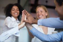 Fim acima dos empregados diversos que juntam-se à mão, dando altamente cinco foto de stock royalty free