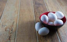 Fim acima dos ovos brancos da galinha, dentro de uma bacia, em uma tabela de madeira foto de stock