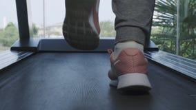 Fim acima dos pés da mulher nas sapatilhas cor-de-rosa na Escada rolante na gin?stica Movimento da c?mera do slider para a frente fotografia de stock royalty free