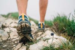 Fim acima dos pés do viajante da imagem em botas trekking no trajeto rochoso da montanha em horas de verão imagens de stock