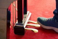 Fim acima dos pés dos homens novos que jogam em pedais do piano fotografia de stock royalty free
