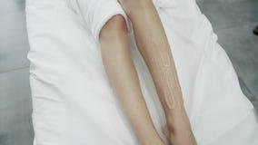 Fim acima dos p?s da mulher cobertos com o gel na tabela branca, procedimento de remo??o de espera paciente do cabelo do laser, m vídeos de arquivo