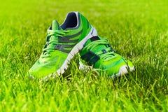 Fim acima dos pares novos de tênis de corrida/sapatas verdes da sapatilha no campo de grama verde no parque imagem de stock