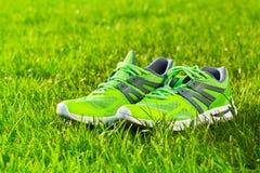 Fim acima dos pares novos de tênis de corrida/sapatas verdes da sapatilha no campo de grama verde no parque foto de stock royalty free