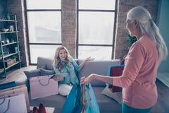Fim acima dos povos bonitos engraçados da foto dois ela seu catálogo da tabuleta da roupa da loja da sala de exposições da neta d imagem de stock