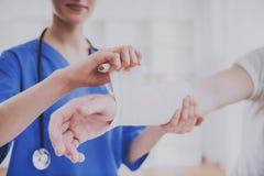 Fim acima Doutor Comforting Hand Inury do paciente fotos de stock