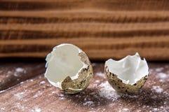 Fim acima Escudo de ovo quebrado das codorniz no fundo da placa de madeira marrom Copie o espaço fotografia de stock