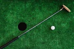 Fim acima Golfe do escritório Clube e bola de golfe de golfe em um curso de mini golfe Imagens de Stock Royalty Free