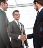 Fim acima homem de negócios novo que agita as mãos com acionista fotografia de stock royalty free