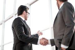 Fim acima homens de negócios que agitam as mãos durante uma conversação no escritório imagem de stock