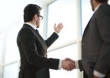 Fim acima homens de negócios que agitam as mãos durante uma conversação no escritório fotos de stock royalty free