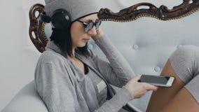 Fim acima A moça senta-se no sofá que veste fones de ouvido pretos e que escuta a música do telefone Mulher do moderno vídeos de arquivo