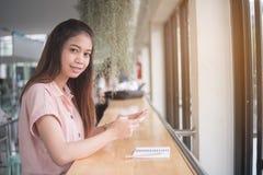 Fim acima Mulher que senta-se na mesa usando o telefone esperto, olhando a câmera, mulher asiática bonita do retrato fotos de stock