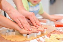 Fim acima nas mãos que fazem as cookies do pão-de-espécie com ajuda da mãe Foto de Stock