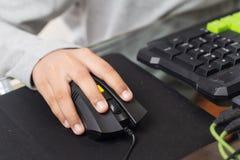 Fim acima no assistente para clicar sobre o rato pela criança do gamer (Sel Imagens de Stock
