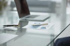 Fim acima programação financeira e penas na tabela no homem de negócios imagem de stock