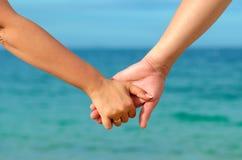 Fim-acima que guardara as mãos com aliança de casamento Foto de Stock Royalty Free