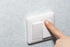 Fim acima Um dedo comprime em um único interruptor da luz branco em uma parede Copie o espaço foto de stock royalty free