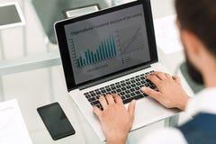 Fim acima um homem de negócios usa um portátil para trabalhar com dados financeiros foto de stock