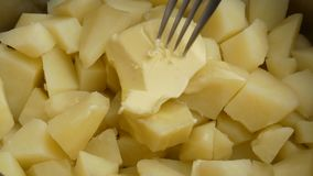 Fim acima Uma grande parte de manteiga manchada com uma forquilha em batatas fervidas filme