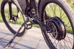 Fim bonde da roda do motor da bicicleta acima com pedal e o amortecedor traseiro imagem de stock