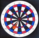 Fim colorido da placa de dardos acima com as setas no bullseye Fotografia de Stock