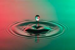 Fim da gota da água acima com vermelho colorido das ondinhas concêntricas e GR Imagem de Stock Royalty Free