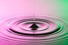 Fim da gota da água com ondinhas concêntricas na superfície cor-de-rosa e verde colorida Imagem de Stock Royalty Free