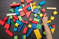 Fim da mão do ` s da criança que joga acima blocos de apartamentos Fotos de Stock Royalty Free
