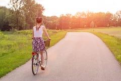 Fim da menina acima com a bicicleta no por do sol do ver?o na estrada no parque da cidade Completando o ciclo a rua para trabalha foto de stock