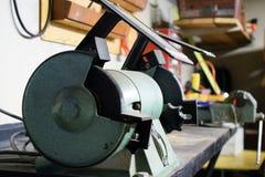 Fim da oficina do metal acima Bench o moedor no primeiro plano, torno no fundo foto de stock royalty free