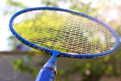 Fim da raquete de badminton acima contra um fundo das árvores foto de stock
