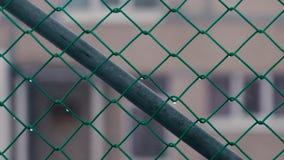 Fim da rede da cerca acima durante a neve e a chuva filme
