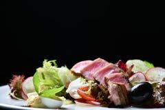 Fim da vista superior acima de fatias passadas ligeiramente raras do atum de Ahi com salada do legume fresco imagem de stock