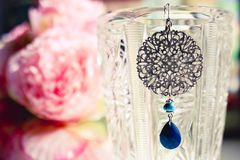 Fim de pedra azul do whith do brinco das senhoras acima com fundo florescido colorido Conceito f?mea fotografia de stock