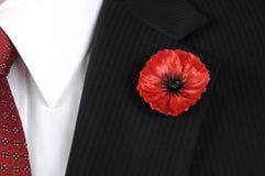 A fim de que não nós esqueçamos Poppy Lapel Pin Badge vermelha no homem preto sira Imagens de Stock Royalty Free