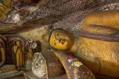 Fim de reclinação da estátua de Buddha acima no templo da caverna de Dambulla, Sri Lanka fotografia de stock