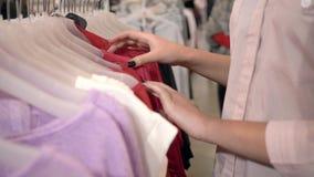 Fim de semana da compra, mãos da roupa nova de consideração fêmea da forma do comprador em ganchos na loja durante a estação das  filme