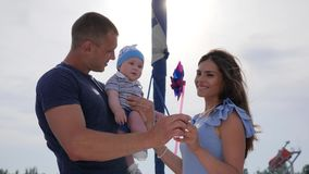 Fim de semana do homem com esposo e criança fora, criança nas mãos do paizinho próximo à mãe no ar livre, video estoque