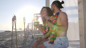 Fim de semana do verão no recurso tropical, a mulher de riso com o homem da colar floresce no pescoço, jovens tem o resto vídeos de arquivo