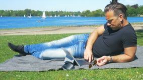 Fim de semana na cidade - um homem relaxa na grama no parque e surfa a Web vídeos de arquivo