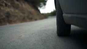 Fim dianteiro esquerdo do pneu do ` s do carro acima do vídeo em uma estrada torcida video estoque