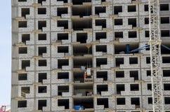 Fim do canteiro de obras acima Nos assoalhos médios, os trabalhadores descarregam materiais de construção fotos de stock