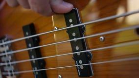 Fim do jogador de guitarra-baixo que joga acima o baixo do virtuoso com dedos filme