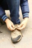 Fim do laço da bota do reparo da mão do menino acima da foto fotografia de stock royalty free